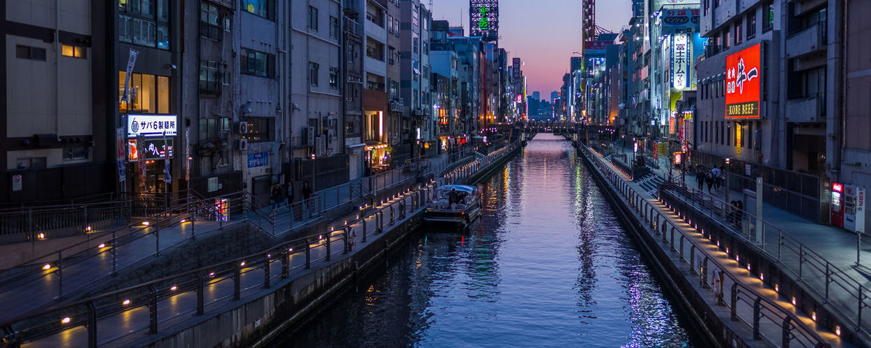 Panoramic view of canal amidst buildings in city at dusk