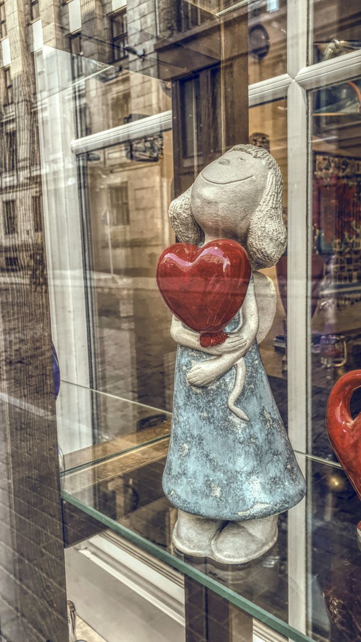 transparent, glass - material, store, no people, human representation, retail, window, representation, reflection, store window, art and craft, sculpture, hanging, indoors, red, choice, day, still life, shelf, shopping, retail display, consumerism
