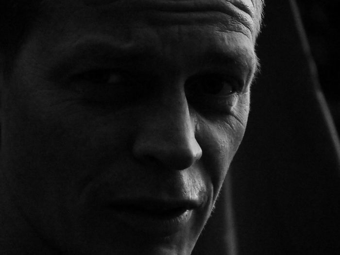 Close-up portrait of handsome young man in darkroom