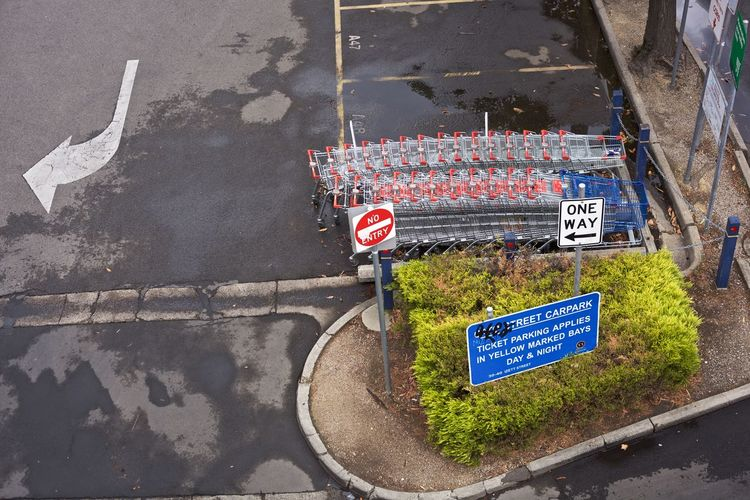 Arrow Architecture Bitumen Blue Sign Bush Carpark Communication Day High Angle View Line And Arrow Lines And Arr No Entry Sign No People Outdoors Red Sign Road Road Sign Shopping Carts Shopping Carts In A Row Shopping Trolleys Shrub Tarmac Text