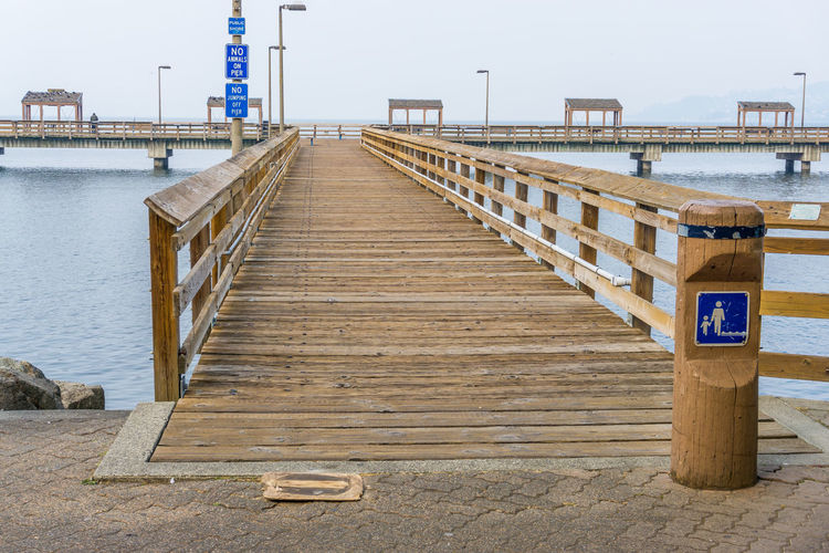 Entrance to a wooden pier. Architecture Beach Bridge Built Structure Clear Sky Communication Connection Day Direction Long Nature No People Outdoors Pier Railing Rustographer Sea Sign Sky The Way Forward Water Wood - Material Wood Paneling