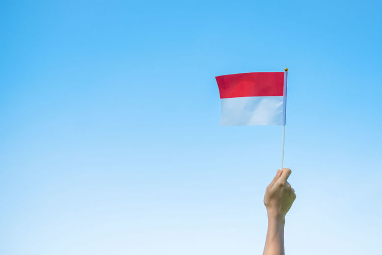 Low angle view of hand holding flag against clear blue sky