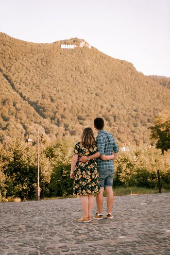 Rear view of couple walking on mountain