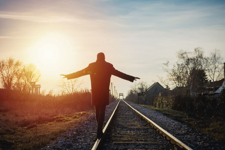Rear view of man on railroad tracks against sky during sunset