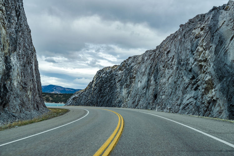 Highway road in the forest, rocks on both sides with mountains in the background. alberta highway 11