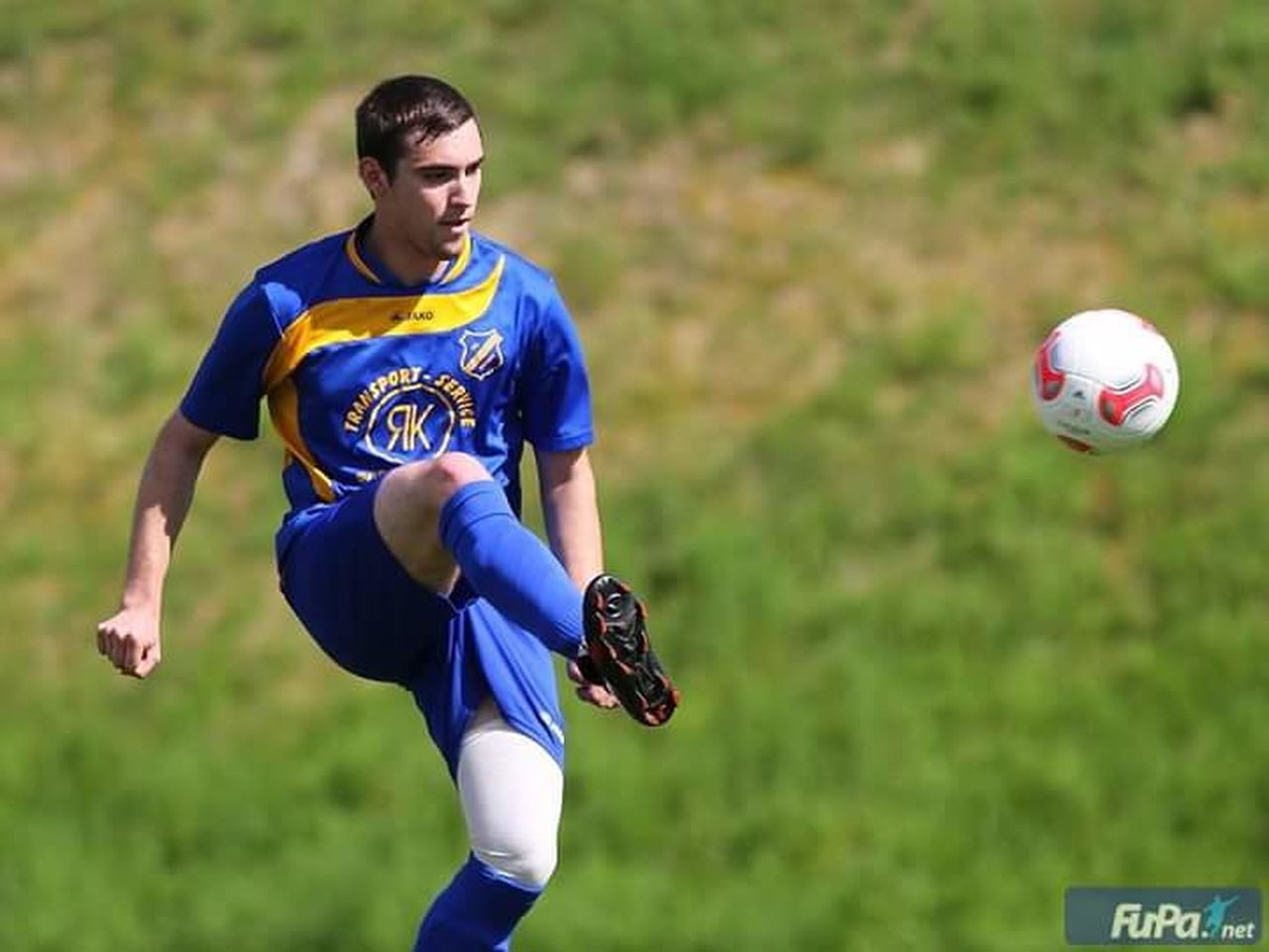 sport, soccer, playing, grass, soccer ball, sports uniform, competition, motion, soccer uniform, kicking, focus on foreground, outdoors, playing field, ball, blue, soccer player, human body part, activity, one person, stadium, competitive sport, skill, match - sport, people, american football - ball, day, adult, sportsman, sports team, soccer field, young adult, only men, one man only, american football player, athlete, adults only, offense - sporting position