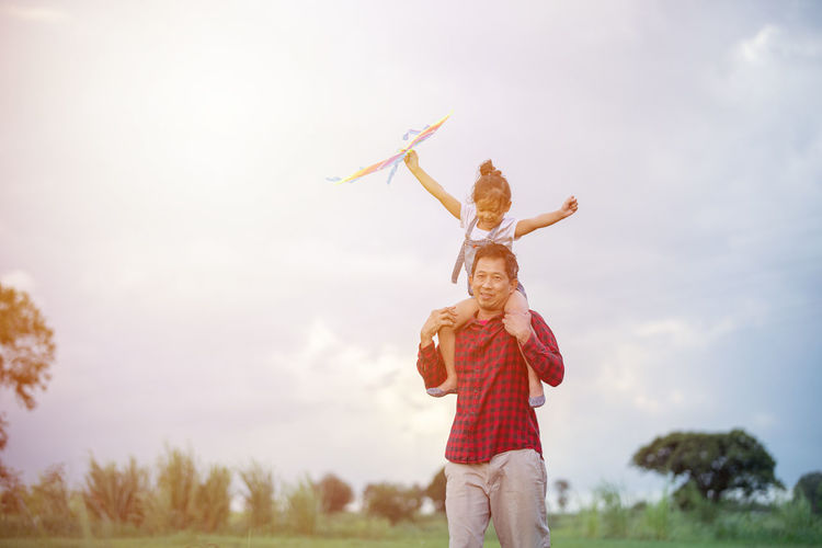 Man giving piggyback ride to daughter against sky