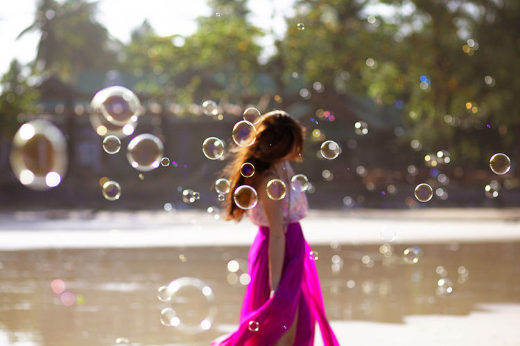 Side view of woman surrounded with bubbles while standing by pond