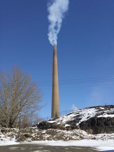 Low Angle View Of Smoke Stack Emitting Pollution Against Blue Sky During Winter