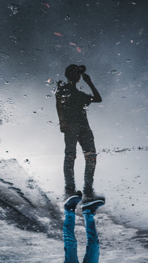 Low angle view of man standing against sky during rainy season