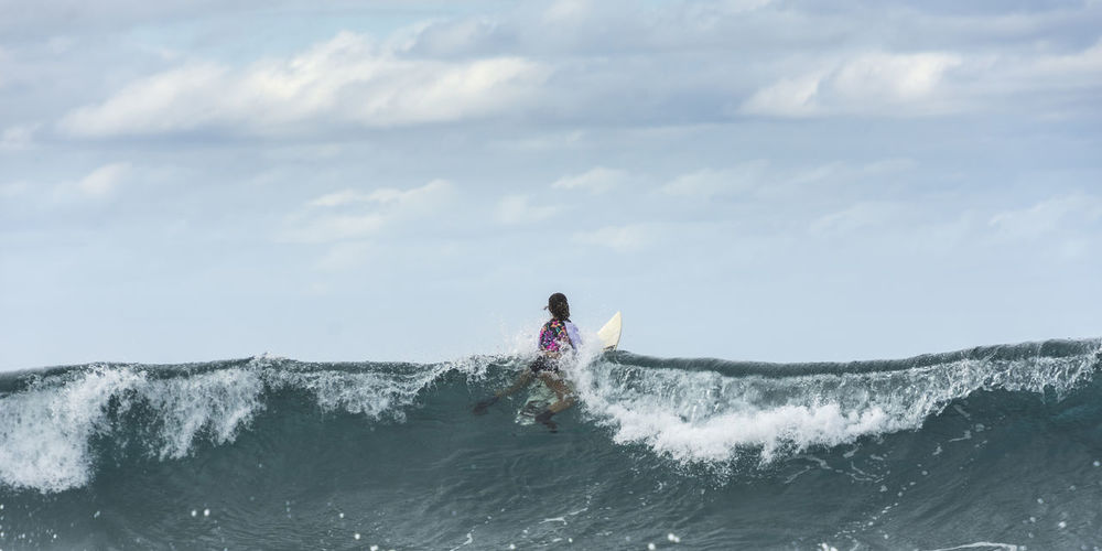 Back view of female surfer at the top of wave