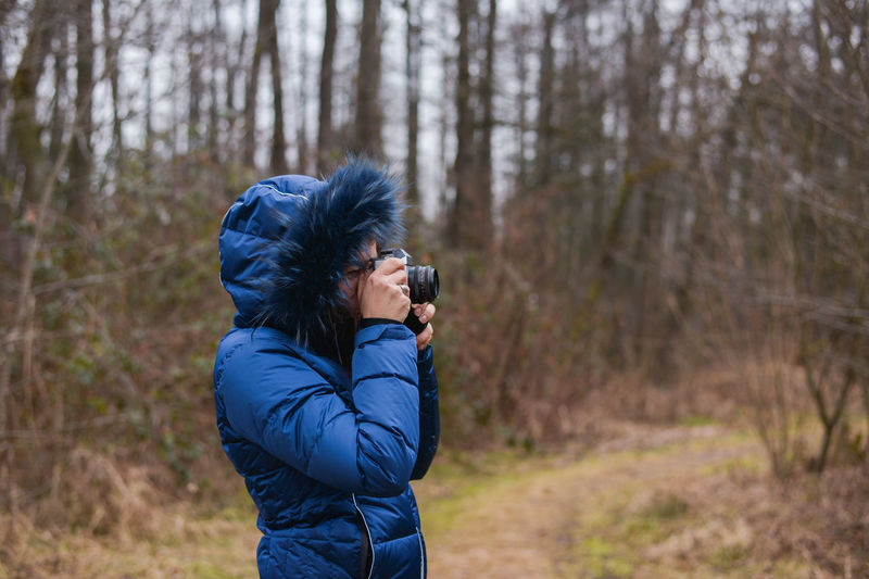 Side View Of Person Photographing With Camera While Standing Against Bare Trees