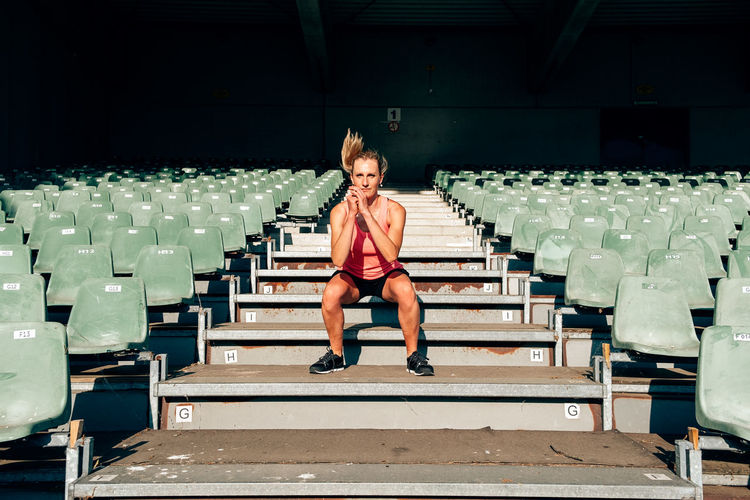 Front view of a fit and healthy woman workingout at the stadium jumping up and down the steps