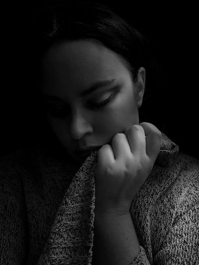 Close-up of woman wearing sweater against black background