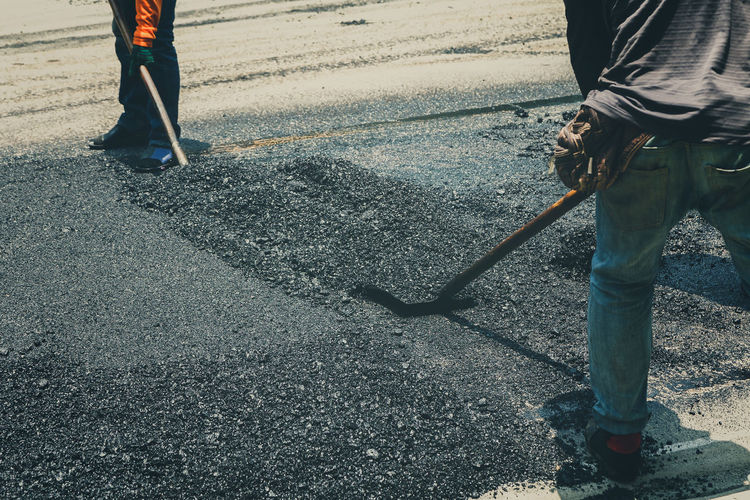 Low section of people working on road in city