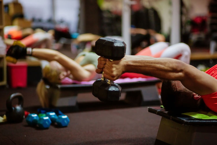 Man and woman exercising while lying in gym