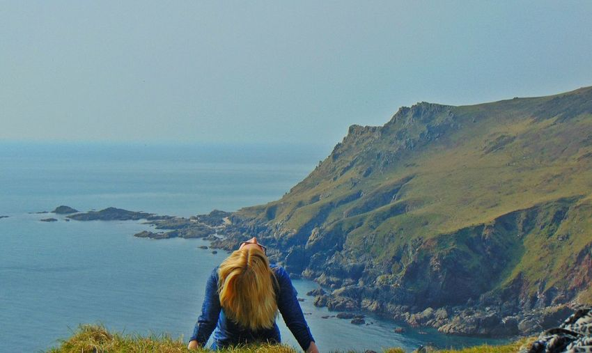 Rear View Of Woman Tossing Hair On Cliff By Sea Against Clear Sky