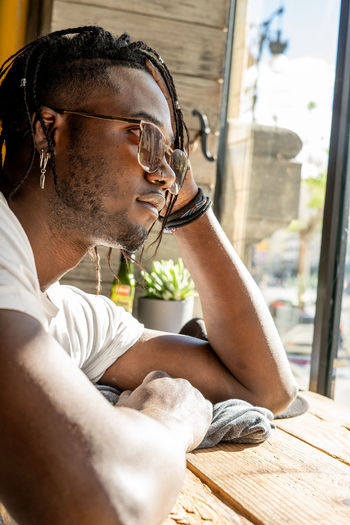 Portrait of young man sitting on window