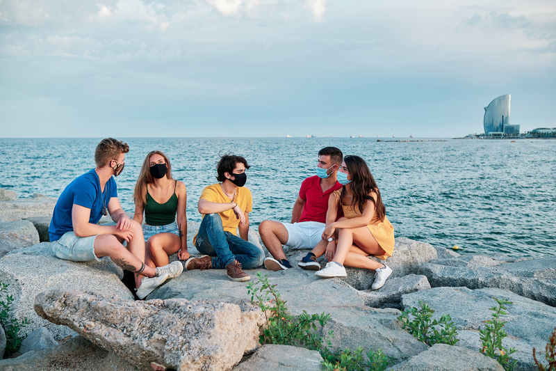 People sitting on rocks by sea against sky