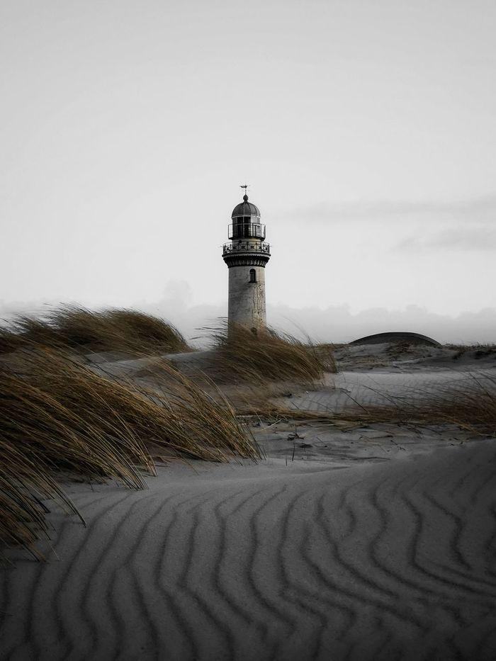 Lighthouse at beach against sky