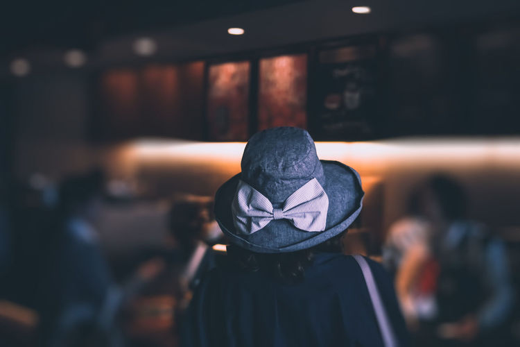 Person wearing hat in cafe at night