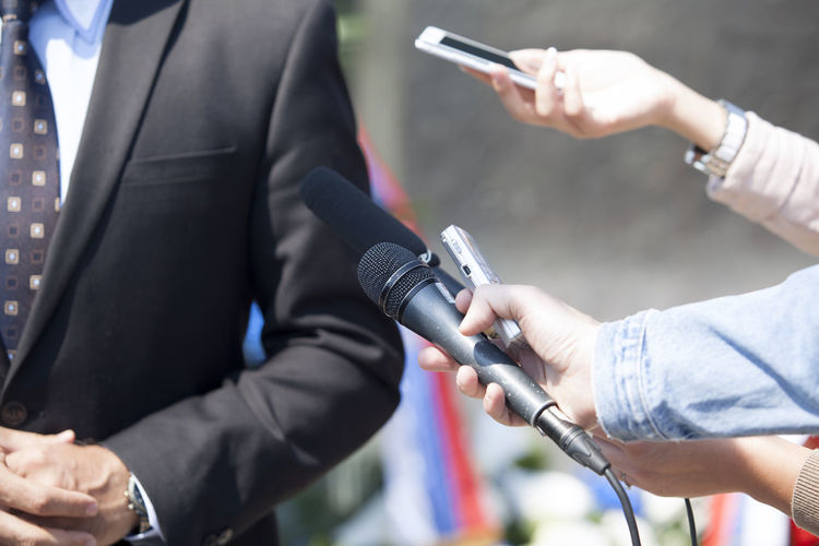 Cropped hand interviewing businessman with microphone