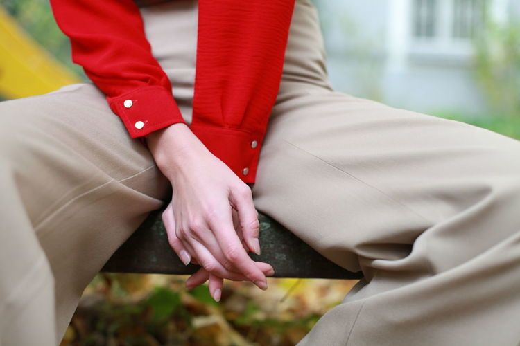 Midsection Of Woman Sitting On Bench