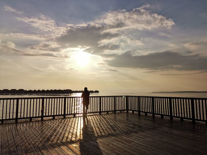 Silhouette man standing on pier over sea against sky during sunset