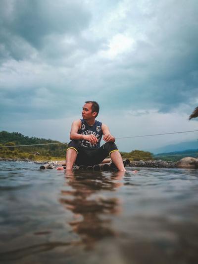 Man sitting in sea against sky