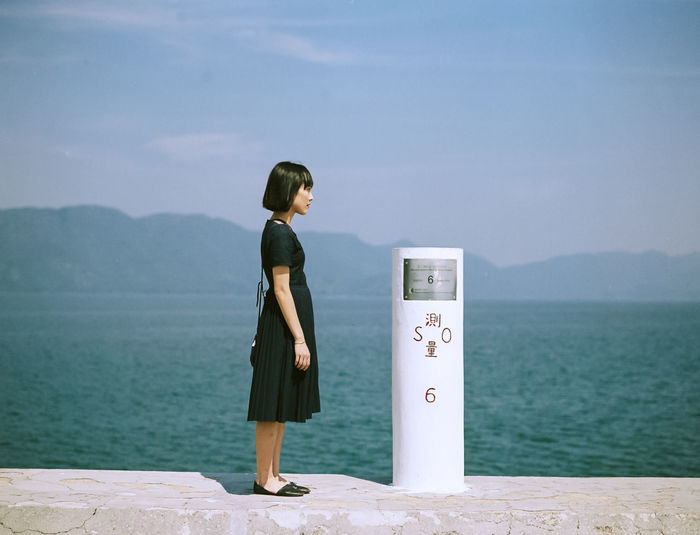 Woman standing by bollard on retaining wall at seaside