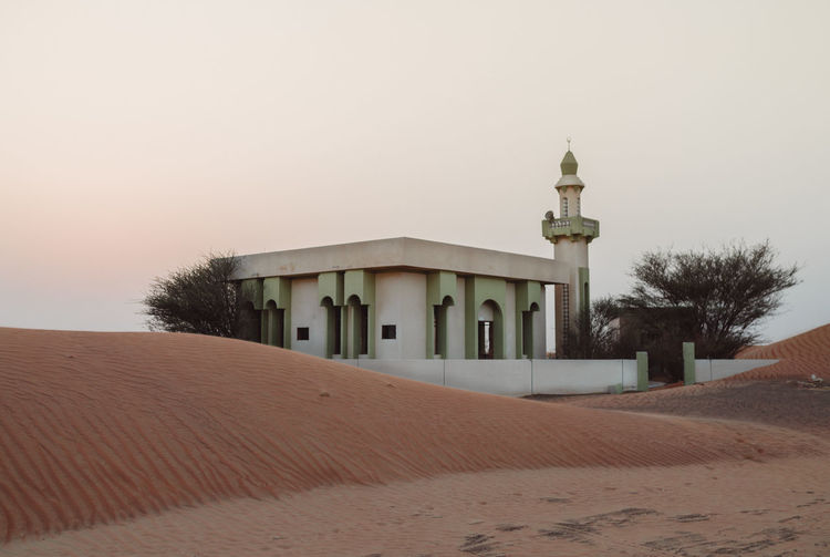Mosque in desert against clear sky