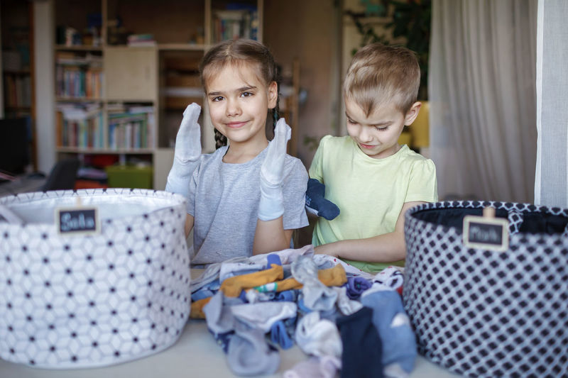 Cute sibling holding dirty clothes at home