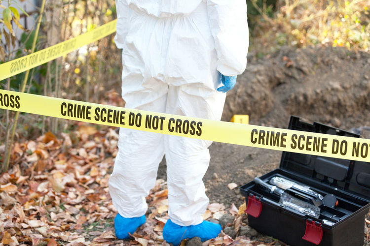 Forensic science specialist standing at a cordoned off crime scene Cordon Tape Crime Scene Crime Law Police Force Security Protection Evidence Detective Dna Investigation Forensic Science Forensic Forensics Protective Workwear Grave Criminologist Criminology Analyse Examine Exhumation Homicide