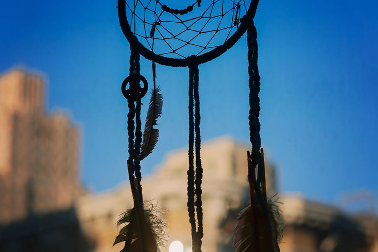 Handmade dream catcher hanging in front of window in a home