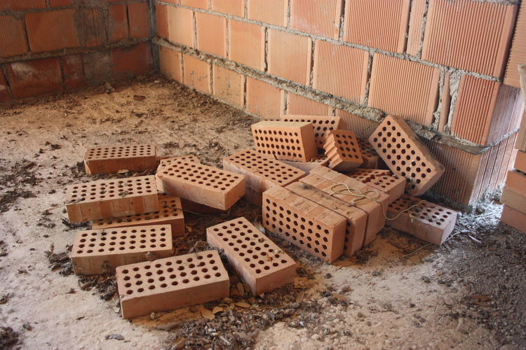 A stack of red bricks to build a residential house within the structure