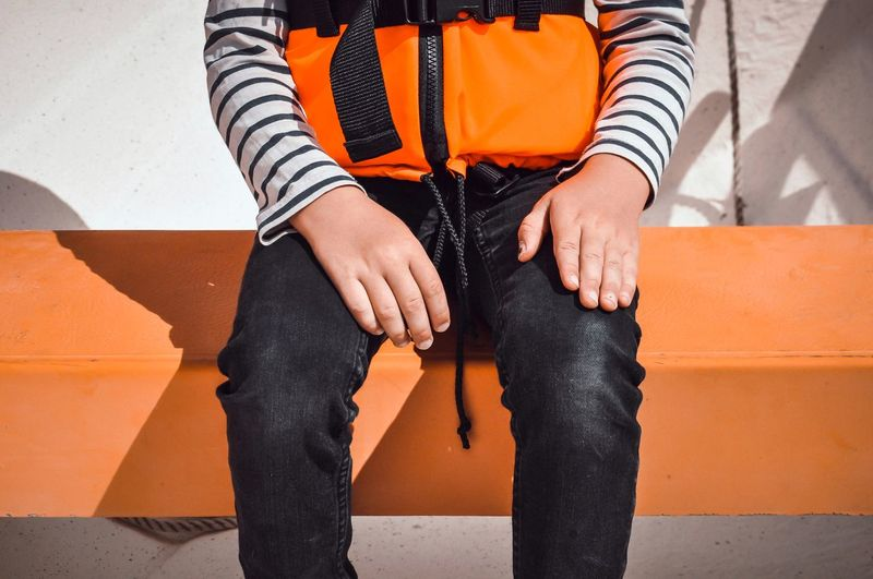 Low section of boy sitting in boat