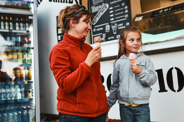 Mother and her daughter eating ice cream sitting on a step in front of food truck during vacations