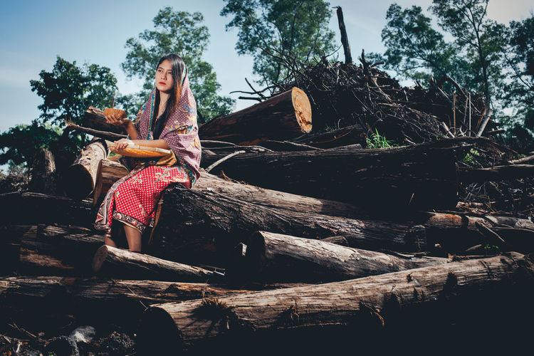 Sad native girl. Her surrounding jungle destroyed by logging activities. Adult Beautiful Woman Casual Clothing Forest Full Length Hairstyle Leisure Activity Lifestyles Log Nature One Person Outdoors Plant Real People Sitting Timber Tree Women Wood Wood - Material Young Adult Young Women The Portraitist - 2018 EyeEm Awards The Photojournalist - 2018 EyeEm Awards