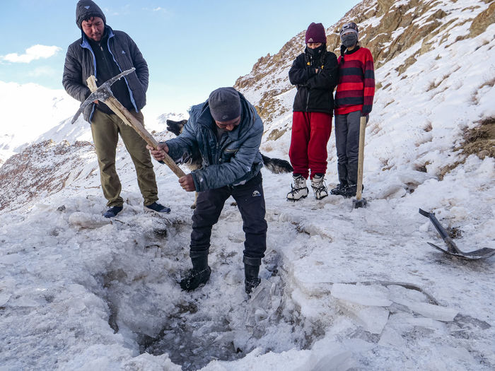 Full length of man standing on snowcapped mountain