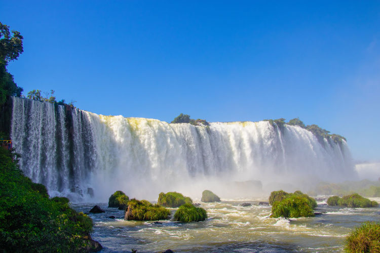 Scenic view of waterfall against blue sky