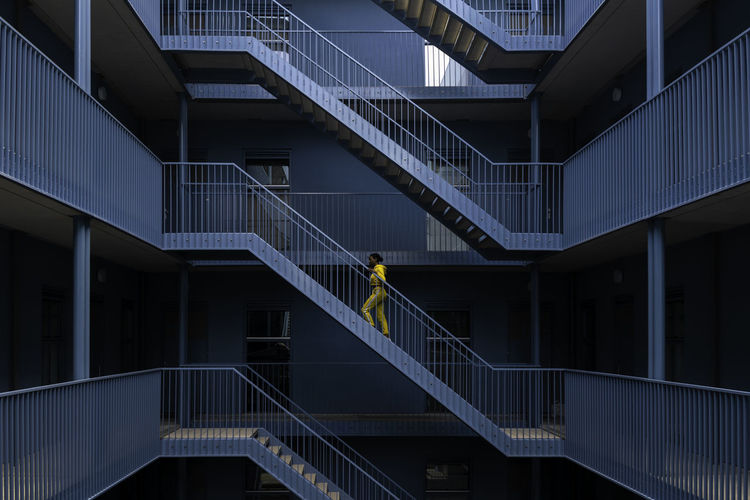 Woman with yellow tracksuit in blue building 001 Composition Lines Woman Architecture Beautiful Woman Blue Building Building Exterior Built Structure City Clothing Contrast Day Lifestyles Modern One Person Outdoors Perspective Photography Railing Real People Staircase Steps And Staircases Tracksuit  Yellow Young Woman