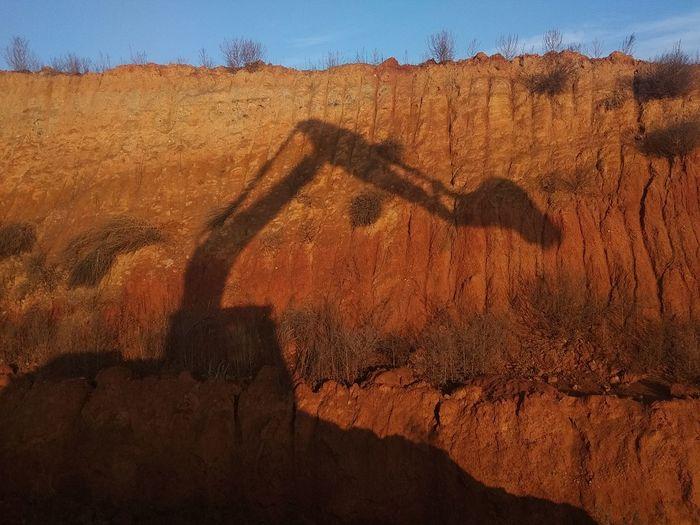 Shadow of excavator on rock