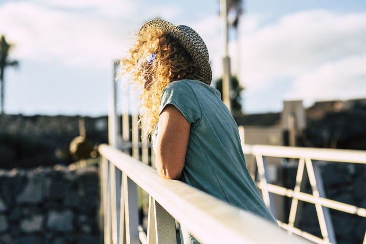 Side view of woman standing against railing