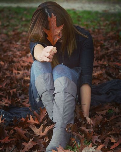Full length of woman showing autumn leaf while sitting on field