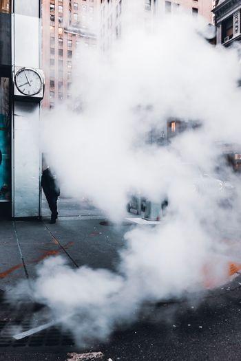 Smoke emitting from street in city