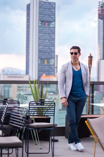 Man in sunglasses standing against cityscape