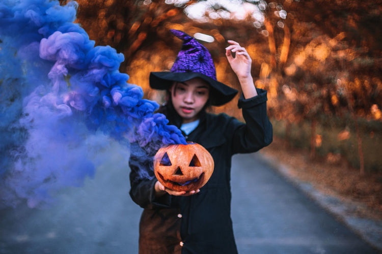 Young woman holding jack o lantern emitting smoke while standing on road during halloween