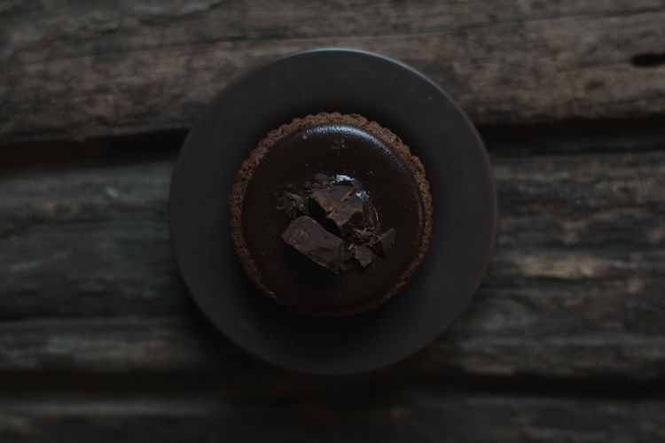 Chocolate Cupcake on Dark Wood Plank Bakery Chocolate Cake Chocolate Cupcake Chocolate Cupcake On Dark Wood Plank Cupcake On Wood Dark Chocolate Cupcake On Dark Wood Dark Chocolate Cupcake On Dark Wood Plank Dark Tcupcake Top View Top View Of Food