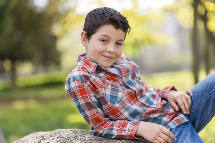 portrait of a casual teen boy, outdoors Portrait Focus On Foreground Real People Sitting Men Casual Clothing Child Looking At Camera Males  Smiling Day Leisure Activity Boys Lifestyles Childhood People Nature Checked Pattern Outdoors Plaid Shirt  Pre-adolescent Child