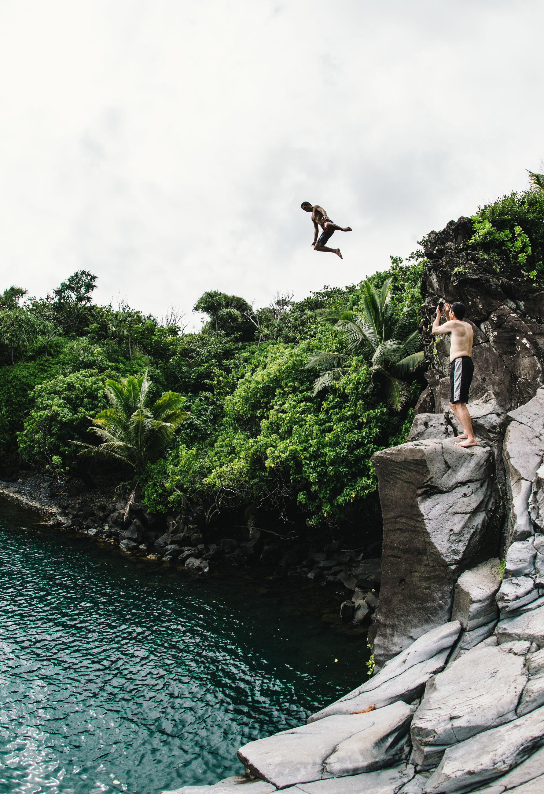 full length, rock - object, day, mid-air, real people, outdoors, tree, men, water, leisure activity, nature, flying, jumping, sky, lifestyles, adventure, low angle view, bird, childhood, beauty in nature, young adult, people